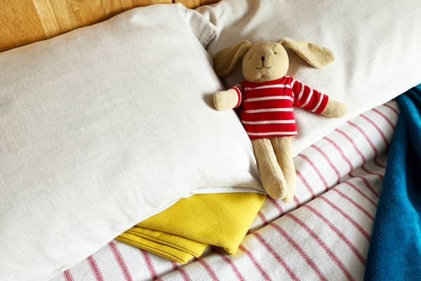 Cozy bed with stuffed bunny on the pillows