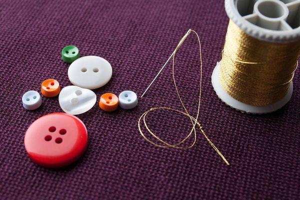 hilo al lado de botones de varios colores y tamaños