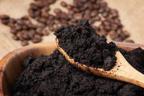 granos de café cobre cuchara en fondo de madera