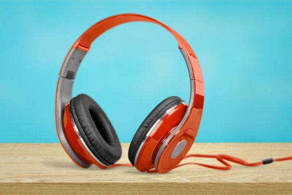 How to recycling electronics: a pair of red electronic headphones resting on a wooden table against a blue background