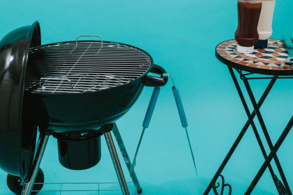 Barbecue naast mozaïektafel met bestek en sauzen erop