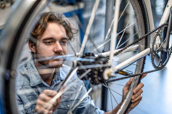 Homem fazendo a manuteção de uma roda com a mão suja de graxa