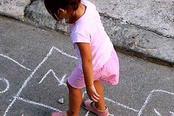 Menina brincando de amarelinha