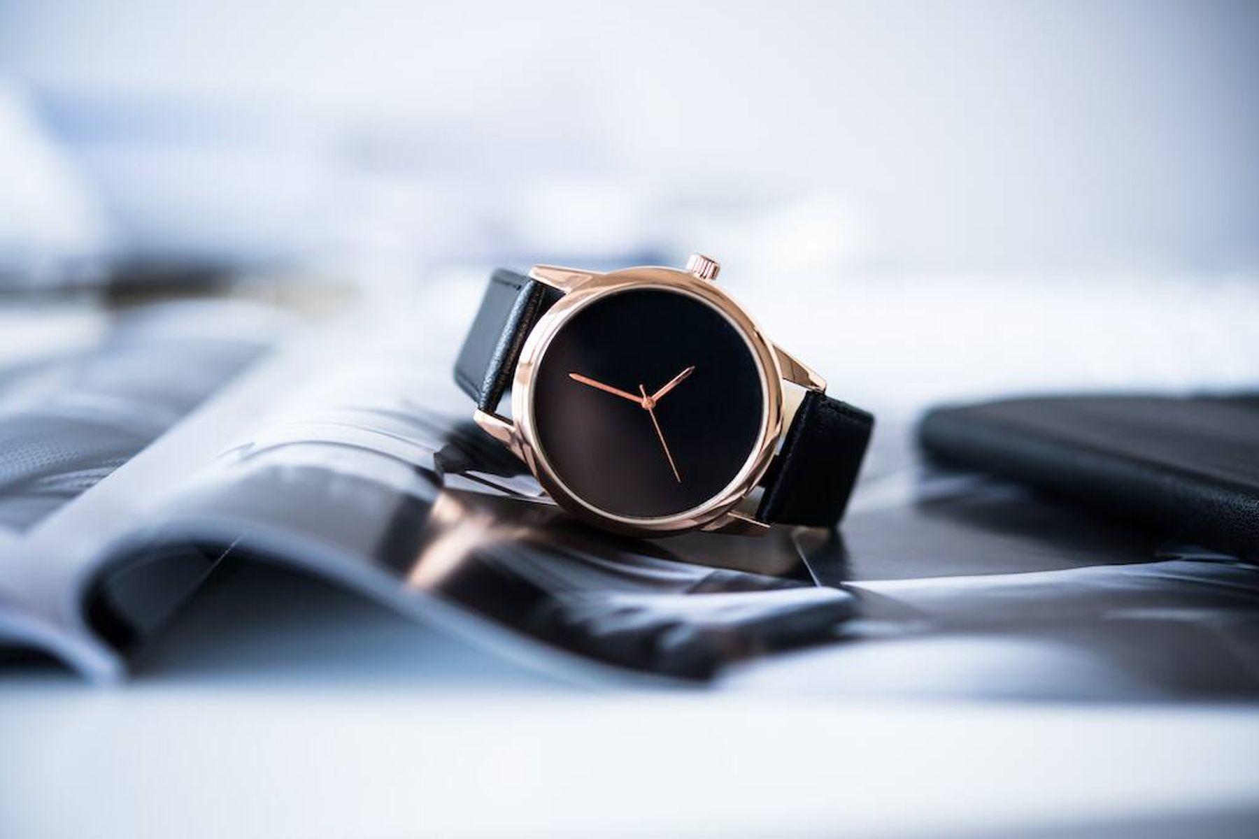czarno-złoty zegarek na rękę nad otwartym magazynkiem