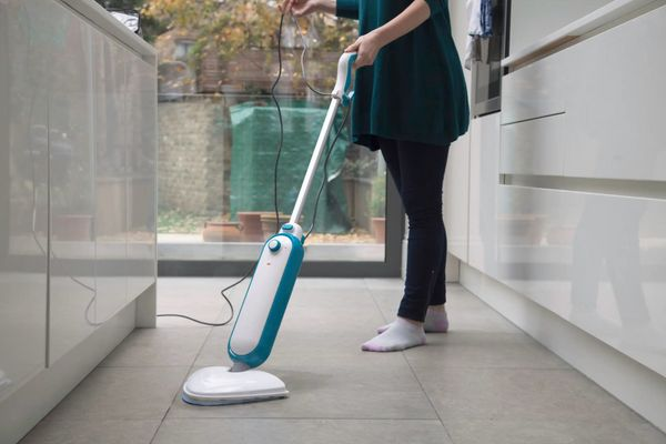 Woman vacuuming kitchen floor