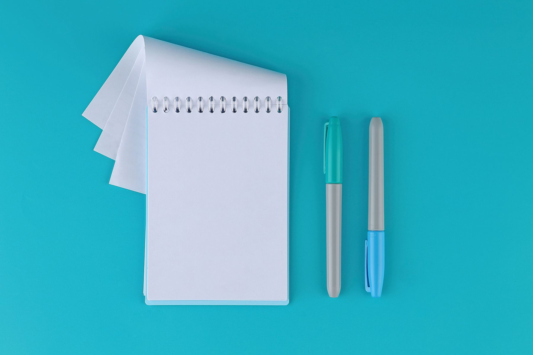 Notepad with two blue pens on blue table