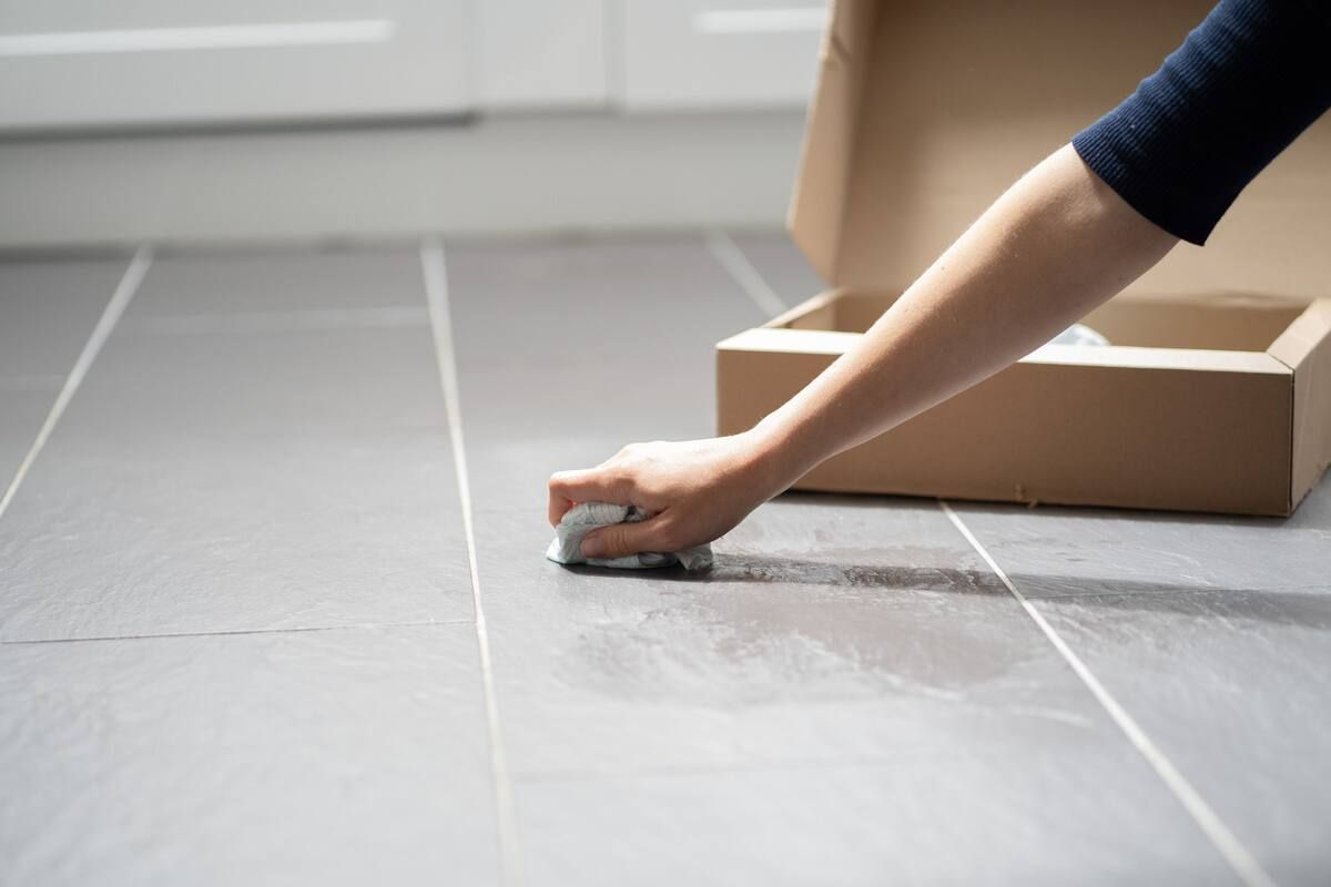 A hand cleaning the floor with a cloth in front of a box containing broken glass