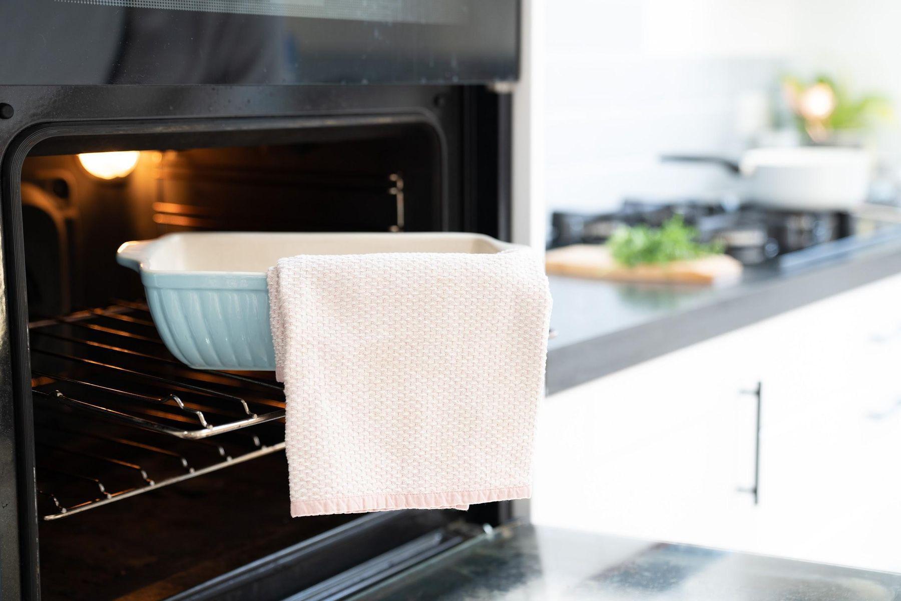 Forno aberto com vasilha de porcelana na prateleira e um pano pendurado