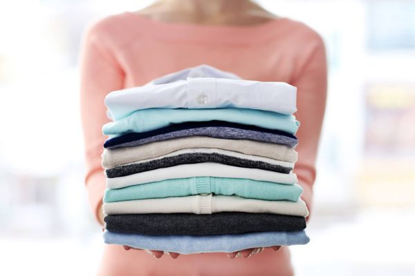 Lady holding a stack of clean laundry