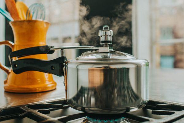 tryckkokare och apelsinpanna med köksredskap