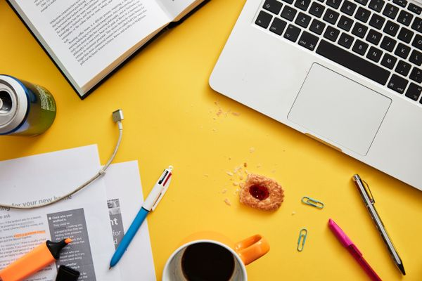 study tips for students: messy desk with laptop, drinks can and food crumbs