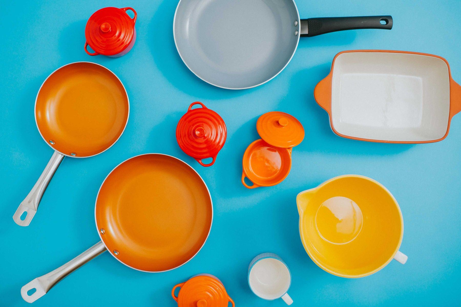 Utensilios de cozinha coloridos sobre mesa azul