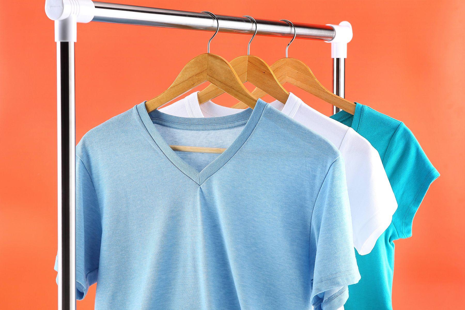 Arara de roupas com uma camiseta azul claro, uma branca e uma azul royal em fundo rosado