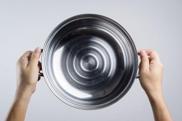 Panela de alumínio vista de cima nas mãos de uma pessoa