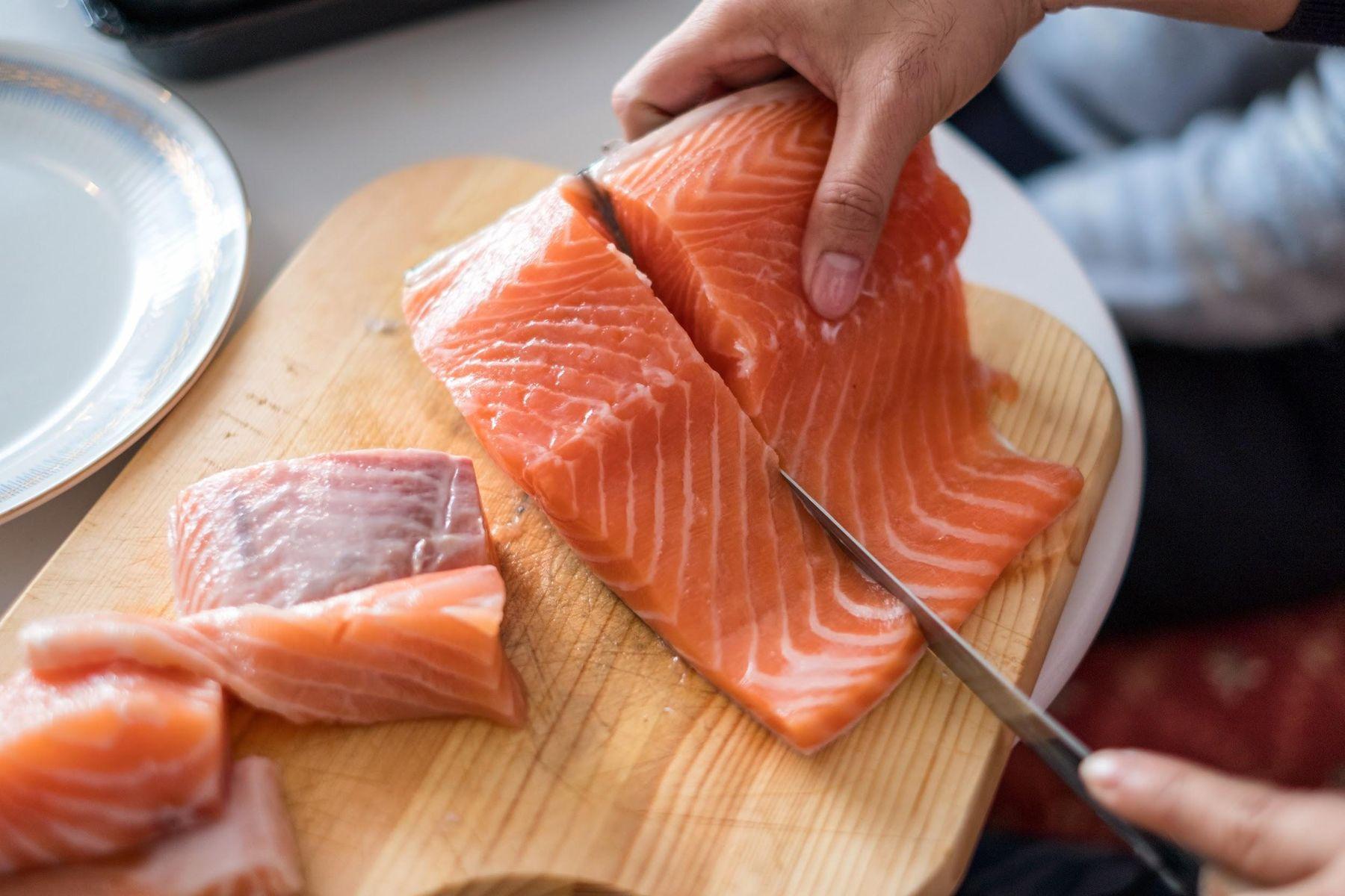 Mulher cortando salmão sobre a tábua de madeira