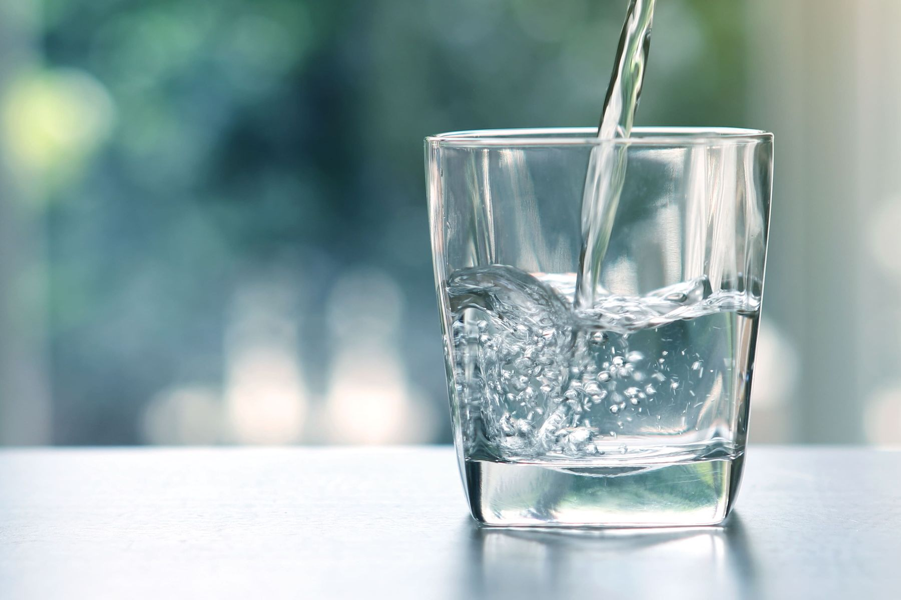 a glass of water in front of a window