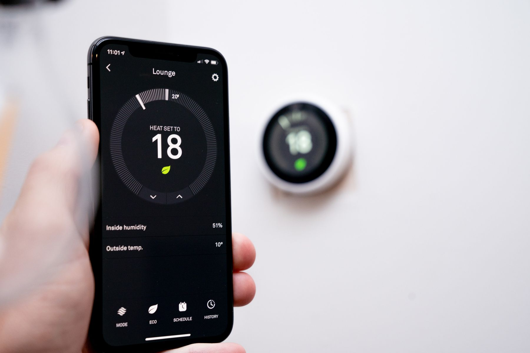 A phone with an app that controls a smart thermostat