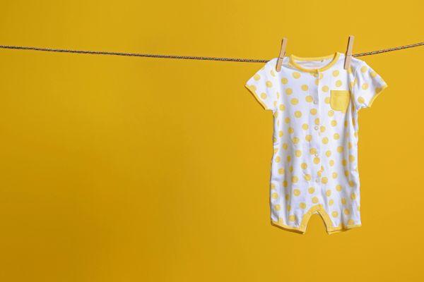 Roupa de bebê lavada e pendurada no varal na frente da parede amarela