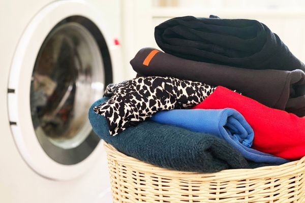 A pile of folded dark laundry in front of a washing machine