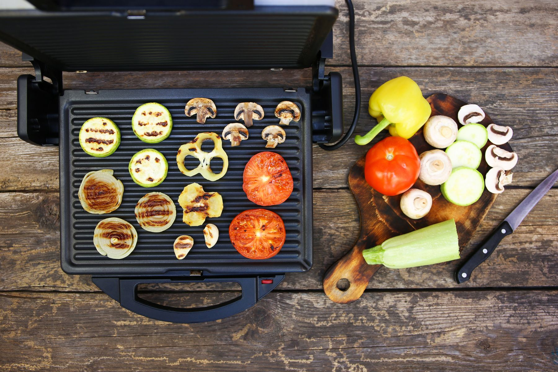 Electric grill with vegetables cooking on it