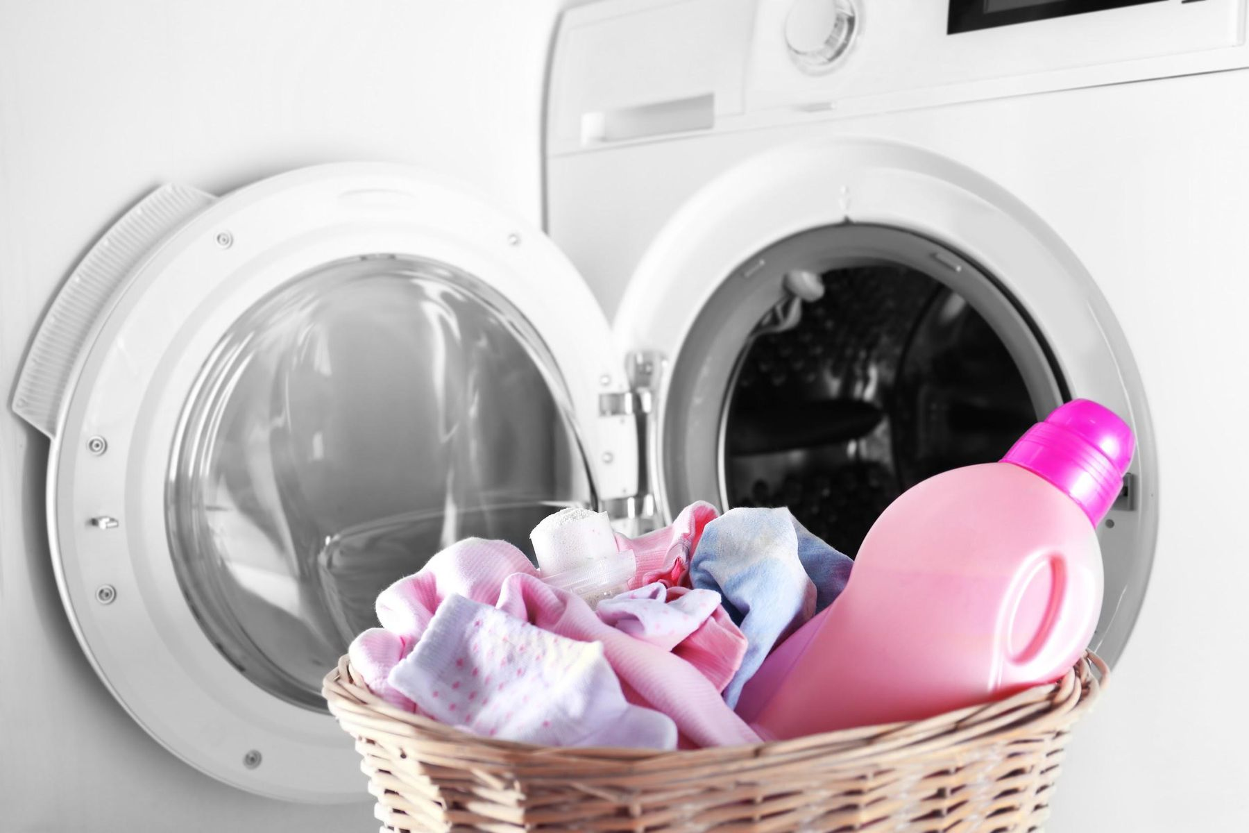 Máquina de lavar e cesto com amaciante e roupas de bebê
