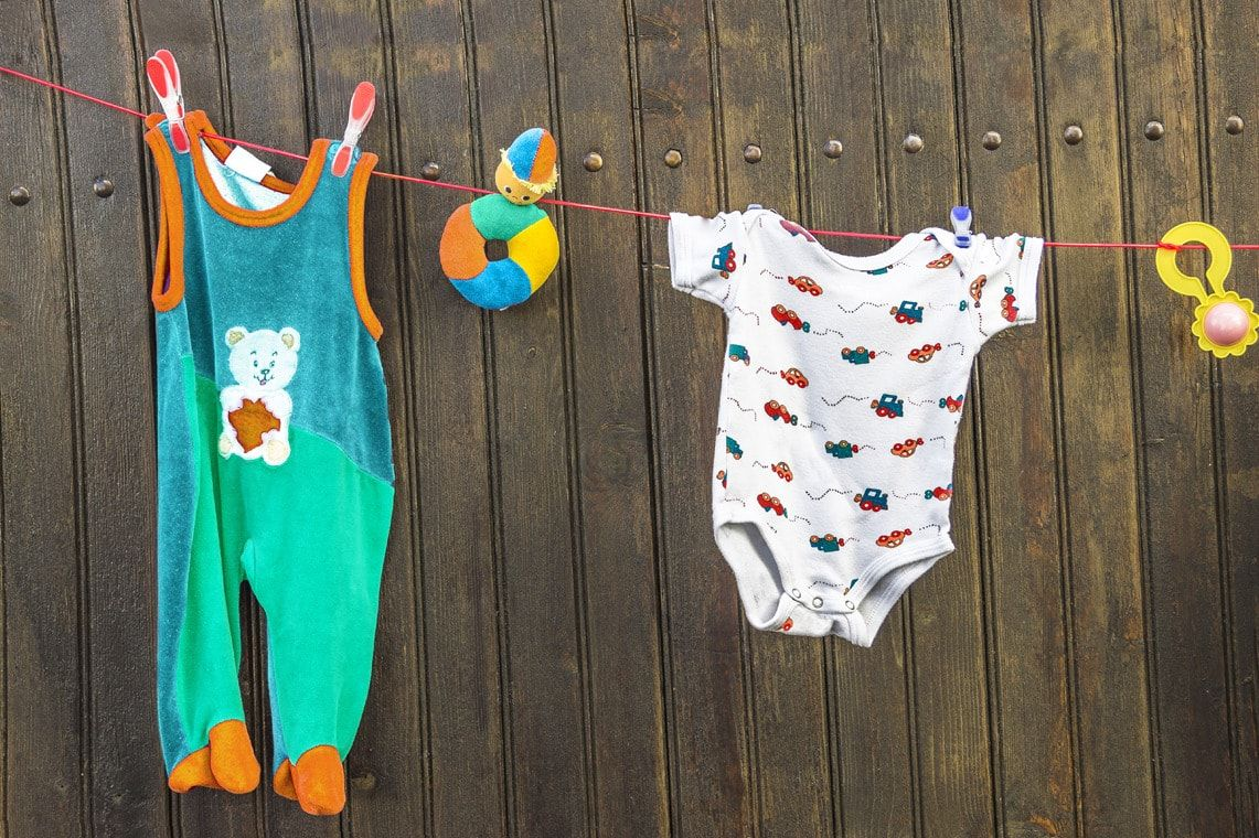 baby clothes and toys hanging on washing line