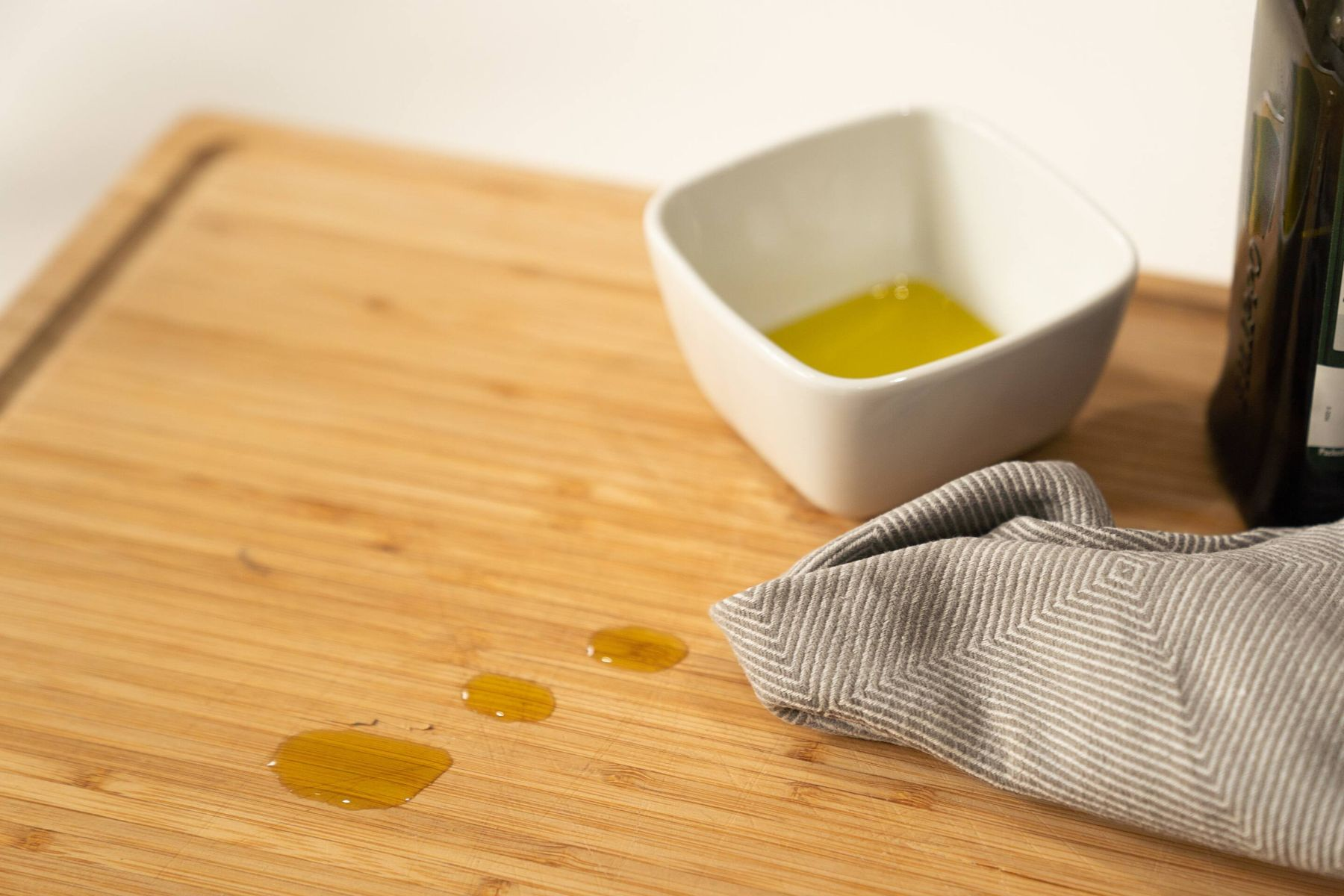 pot with olive oil and cleaning cloth on wooden worktop