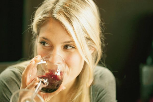 a blond woman drinking red wine