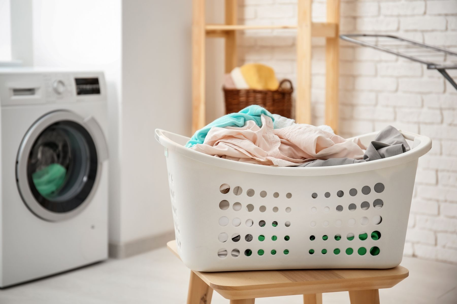 basket of clean laundry with washing machine