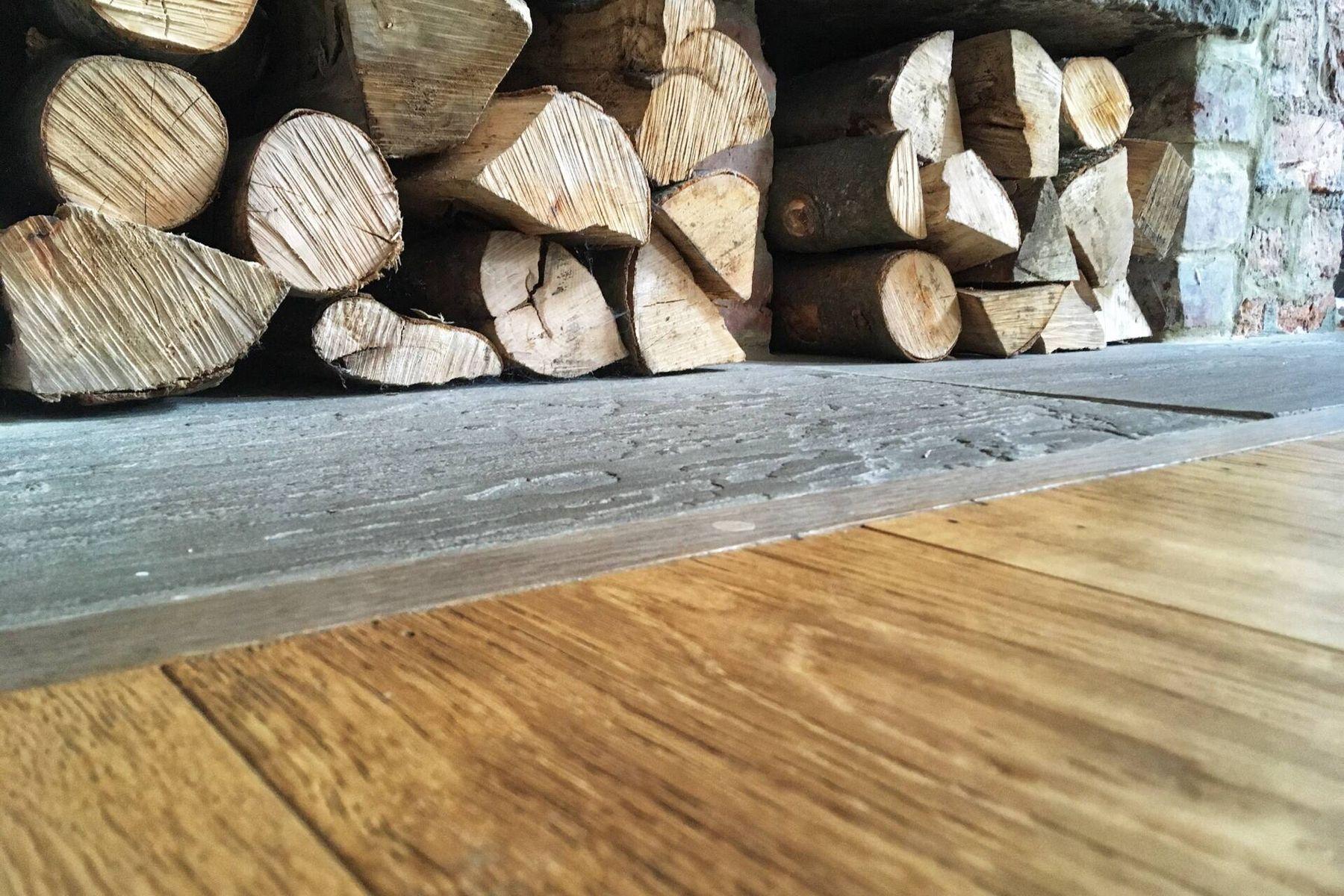 Brennholz geschnitten und unter Steinbank gelagert