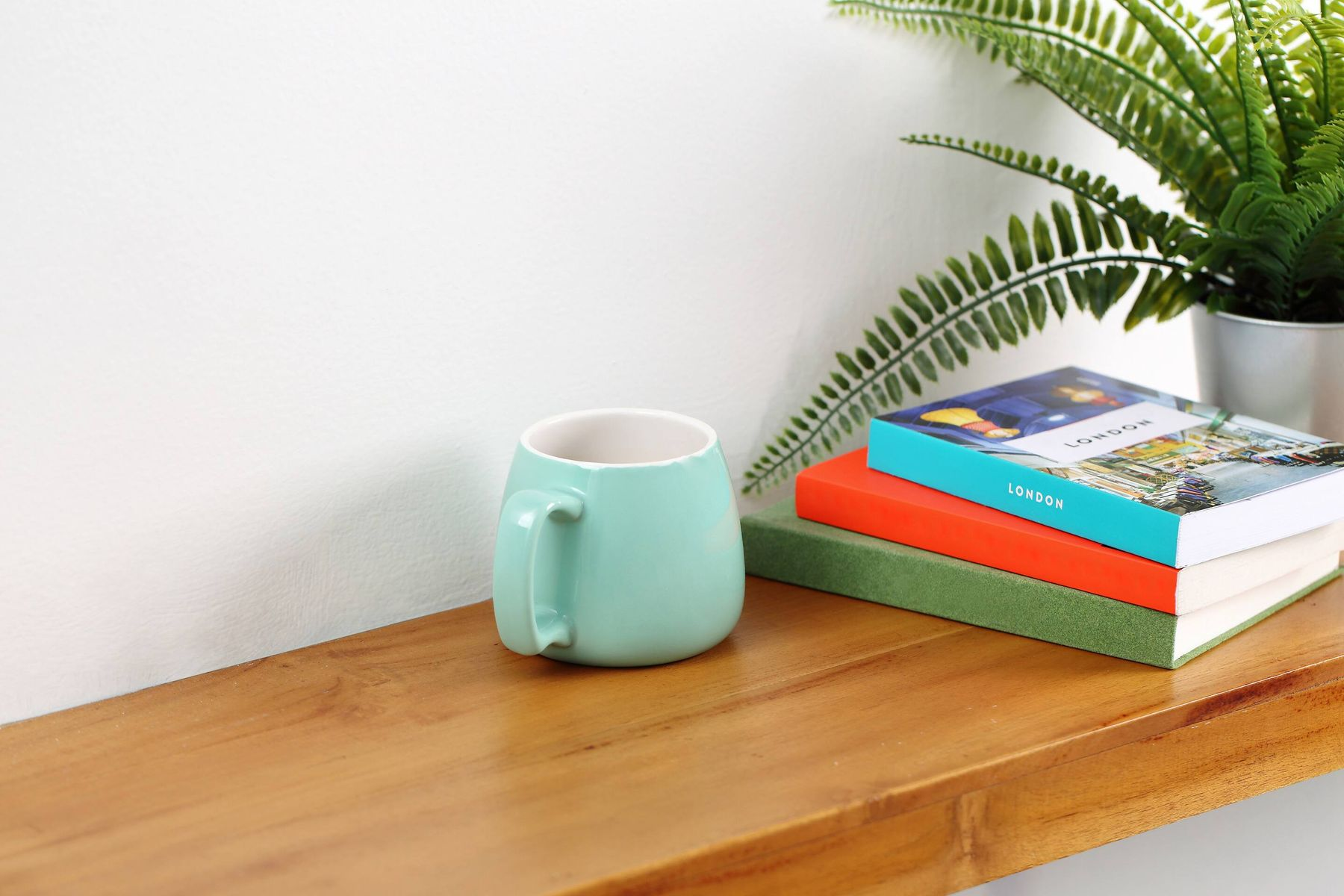 books, porcelain mug and potted plant on wood sideboard