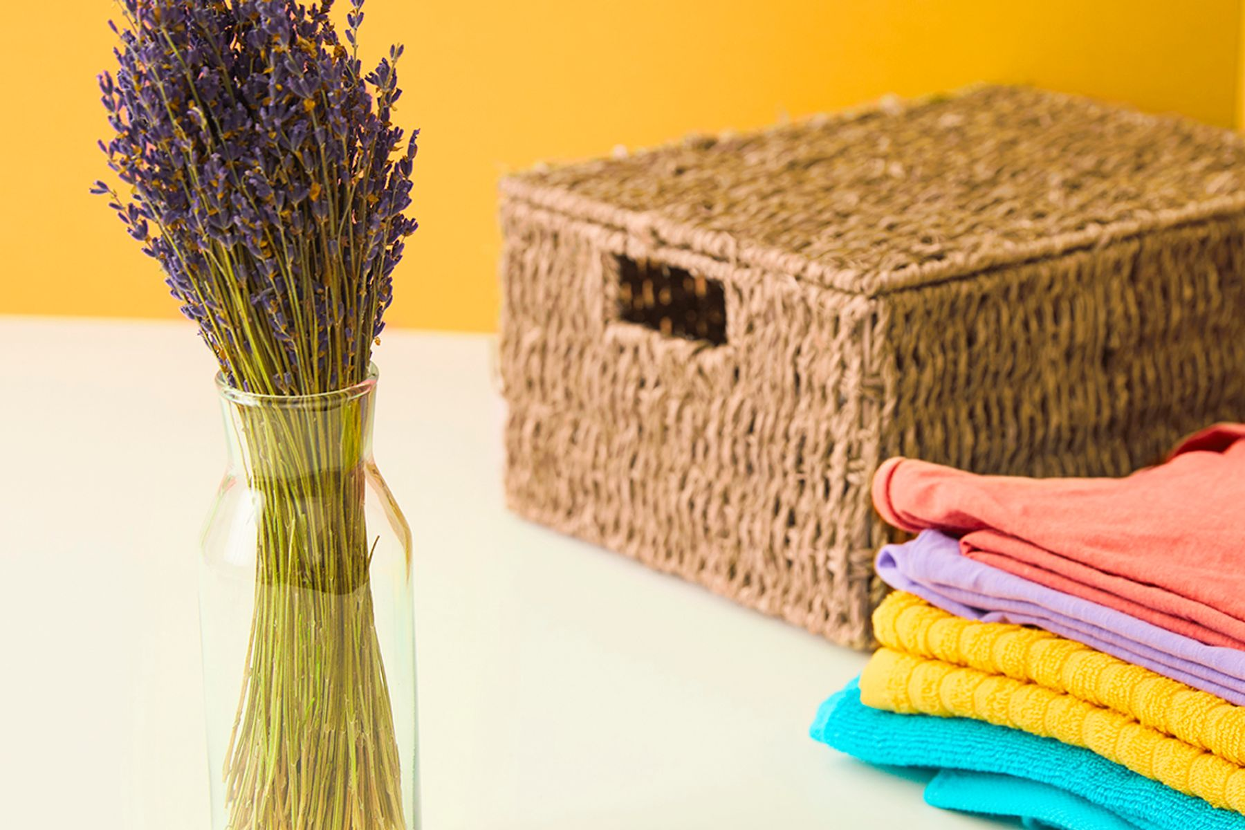 a bunch of dried lavender in a vase as a way of how to keep clothes smelling fresh, in front of wicker basket and towels