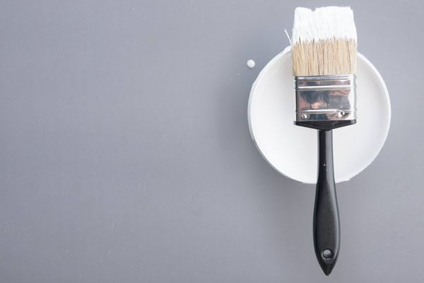 White paint and a paint brush to cover water stains on the ceiling