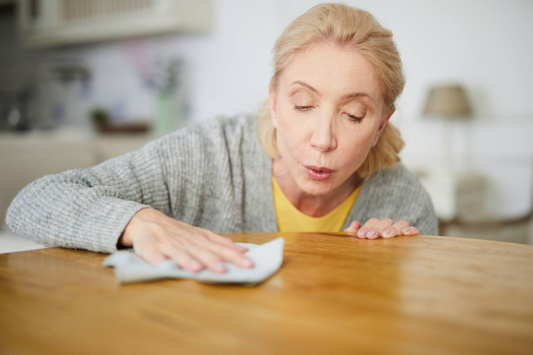 Mulher limpando superfície de madeira com pano branco
