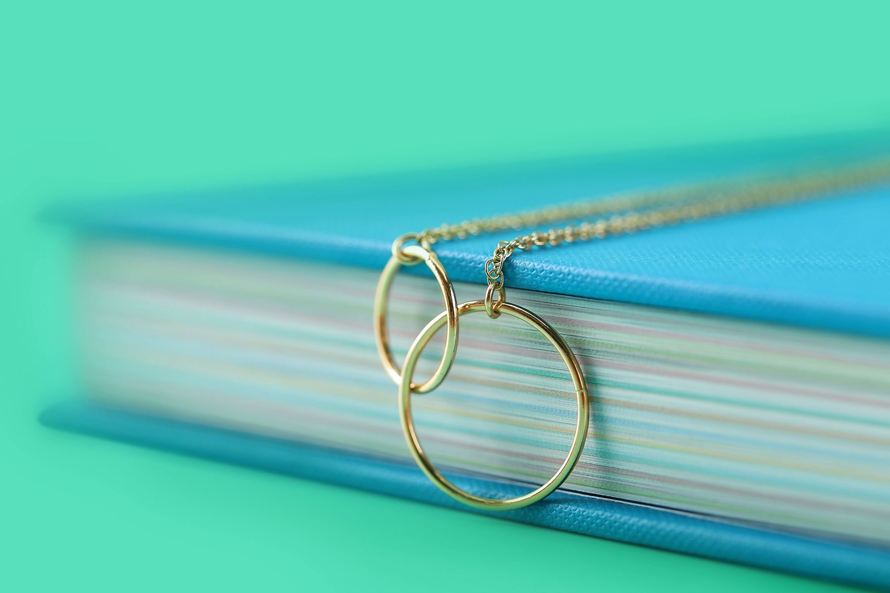 Clean gold necklace chain draped over a book