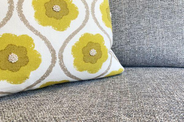 Sofá de tecido com uma almofada florida em cima