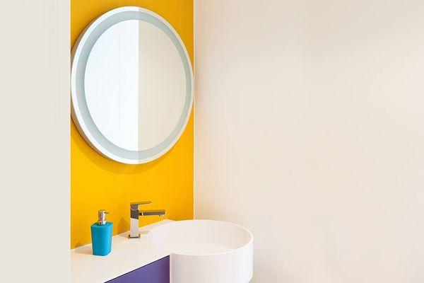 Pia de banheiro branca com frasco azul em cima, e parede amarela com espelho redondo pendurado