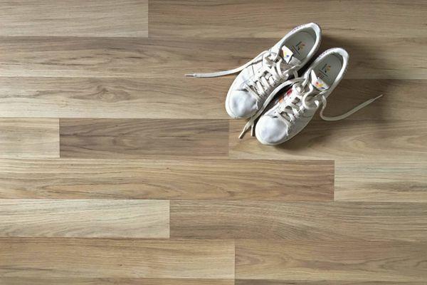 Sepatu putih di atas lantai kayu