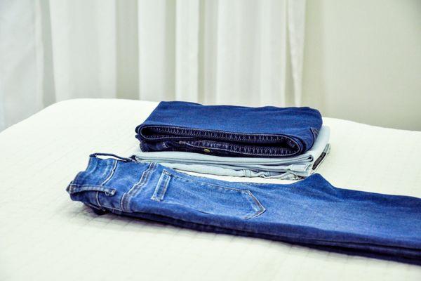 Calças jeans dobradas e esticadas em cima da cama