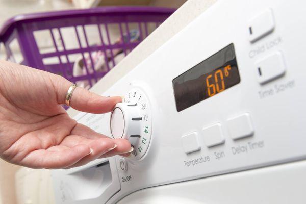 Mano de persona eligiendo un ciclo de lavado y la temperatura en el lavarropas