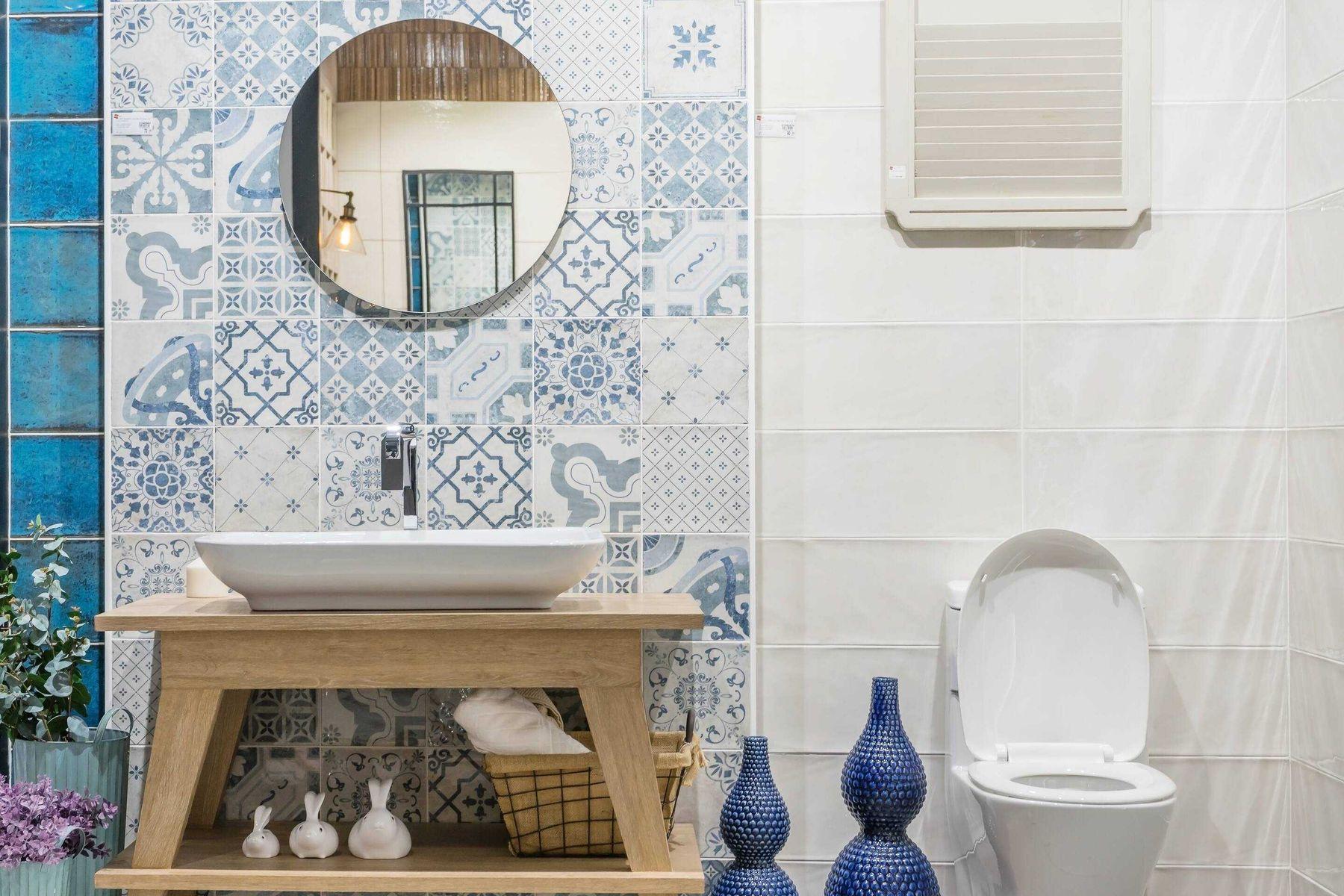 Banheiro com azulejo e decoração azuis e espelho redondo