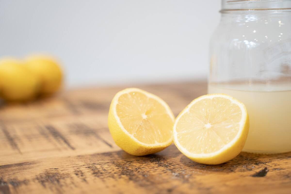 Lemon cut in half in front of a jar of lemon juice