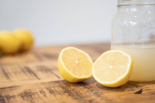 Lemon cut in half in front of a jar of lemon juice