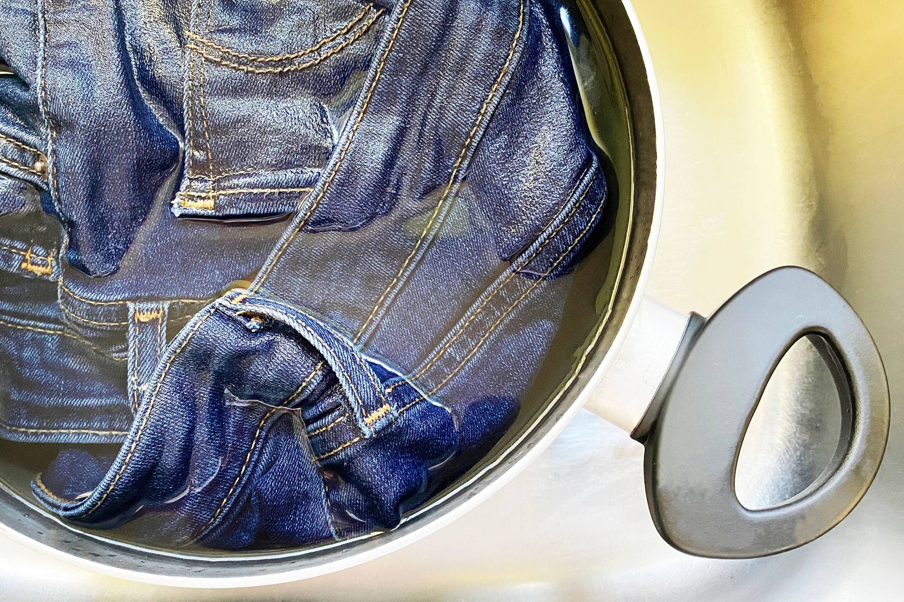 A pair of jeans in a pan of water