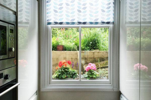 Okno w kuchni z widokiem na ogród z roślinami i kwiatami