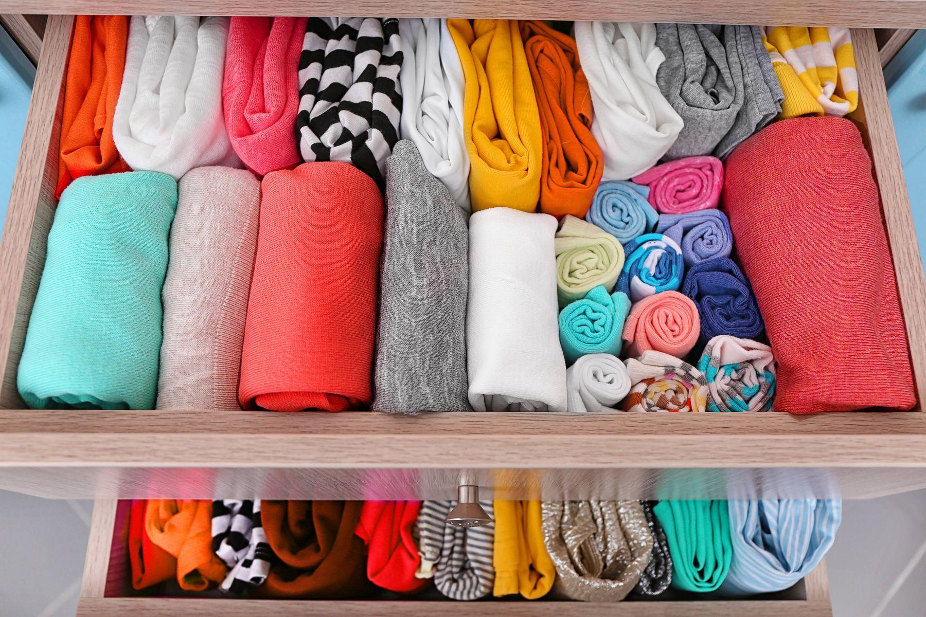 Duas gavetas abertas com roupas coloridas organizadas em rolinhos