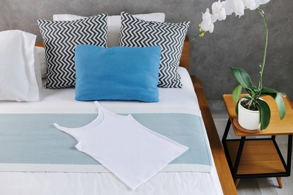 white and blue bedding a bed in a grey bedroom