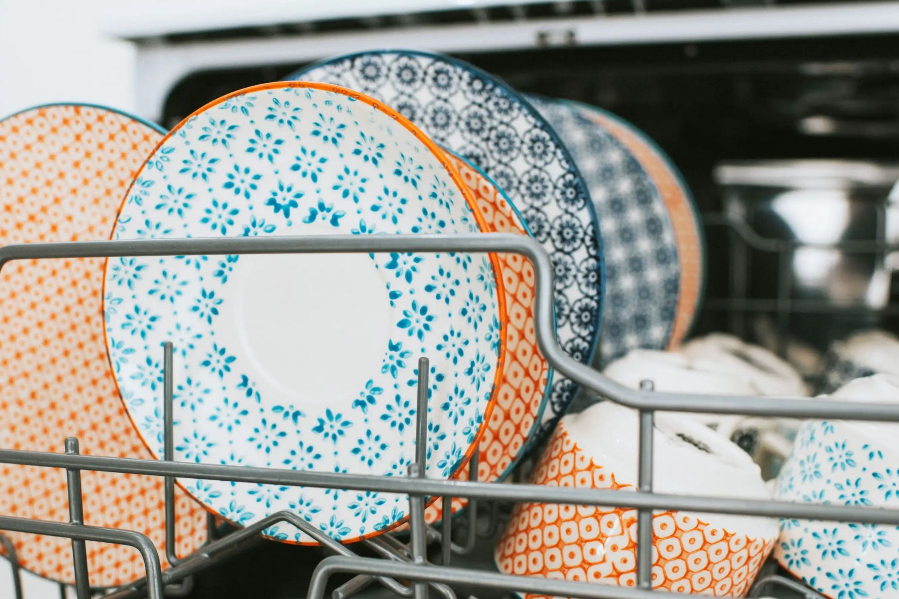 Orange and blue plates stacked in a dishwasher