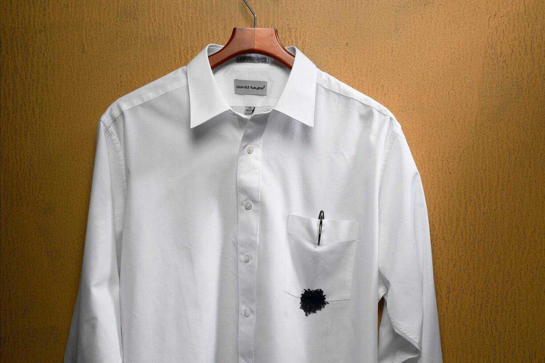 Camiseta branca com botão manchada de caneta