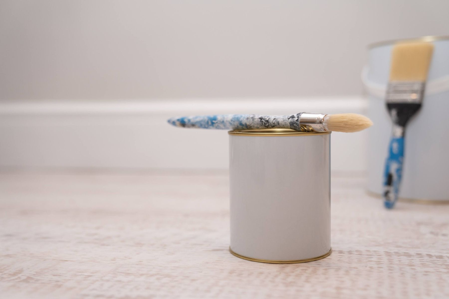 paint cans and brushes on the floor by the wall